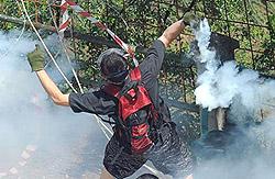 un militante No Tav respinge un lacrimogeno Cs