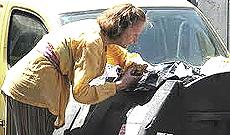 Una donna rovista nella spazzatura