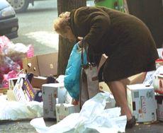 Un'anziana tra i rifiuti di un mercato