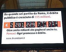 Tabellone sul debito alla stazione ferroviaria Milano Centrale